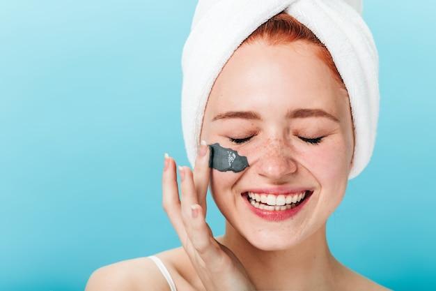 Fille joyeuse appliquant un masque facial avec les yeux fermés. vue de face de la femme excitée faisant un traitement spa isolé sur fond bleu.