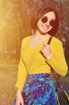 Une fille joyeuse dans un pull jaune vif traverse le sprin