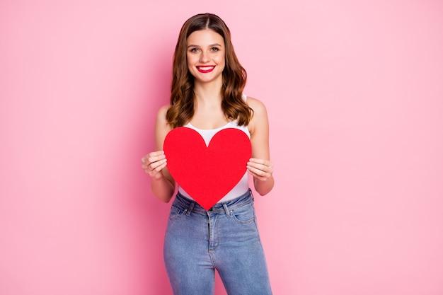 Fille joyeuse positive tenir grand coeur de carte de papier rouge