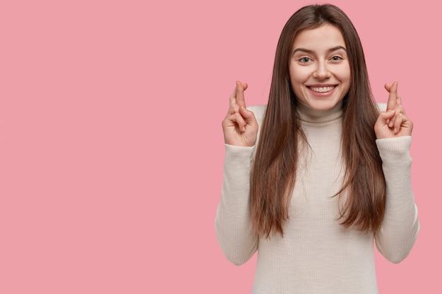 Une fille joyeuse prie avec toute la foi, a croisé les doigts, espère que le plan fonctionnera