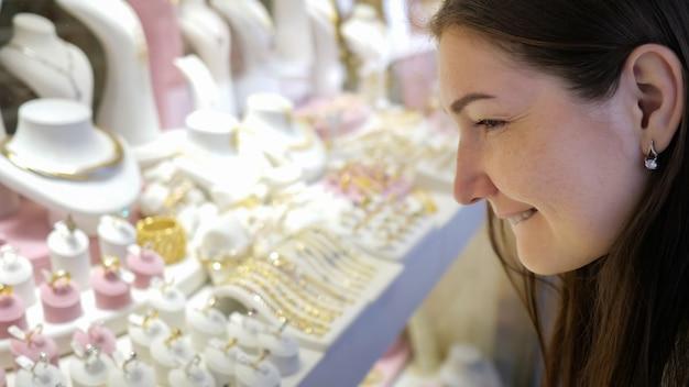 Une fille joyeuse regarde de magnifiques bijoux coûteux dans une vitrine et fait son choix dans un magasin moderne, vue extrêmement rapprochée