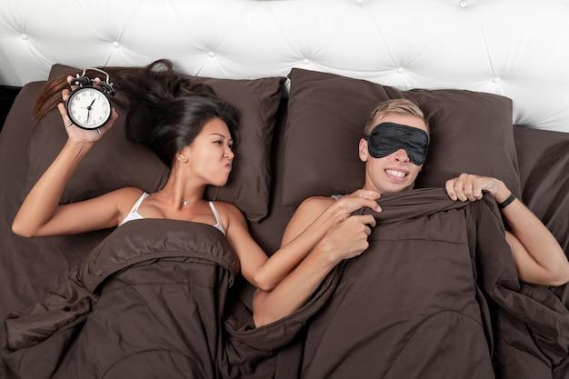 Une fille joyeuse réveille son jeune homme avec l'encouragement d'un réveil