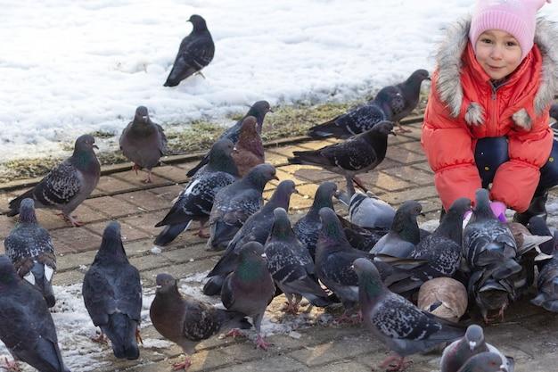 Une fille joyeuse et surprise se nourrit avec les mains des pigeons d'hiver dans le parc elle s'est accroupie
