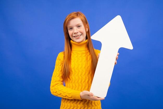 Fille joyeuse tenant une flèche en papier avec une direction vers le haut sur bleu