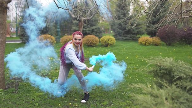 Une fille joyeuse vêtue d'une chemise et d'un jean avec des tresses arc-en-ciel lumineuses et un maquillage inhabituel. elle danse en se cachant dans une épaisse fumée artificielle bleue sur fond de parc printanier