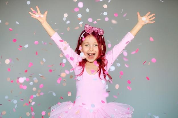 Fille de joyeux anniversaire avec des confettis sur fond gris