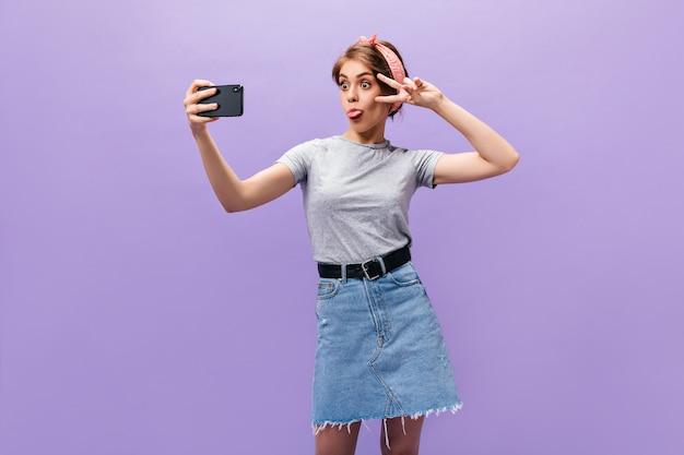 Fille en jupe en jean montre la langue, montre le signe de la paix et prend selfie. femme drôle de bonne humeur dans des vêtements élégants posant.