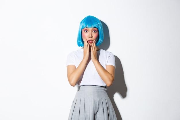 Fille kawaii asiatique surprise en perruque courte bleue, haletante étonnée, tenant la main près de la bouche et regardant la caméra, vêtue d'un costume d'halloween, debout.