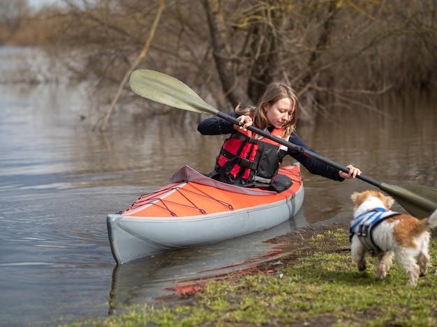 Une fille sur un kayak rouge navigue du rivage en poussant avec une rame.