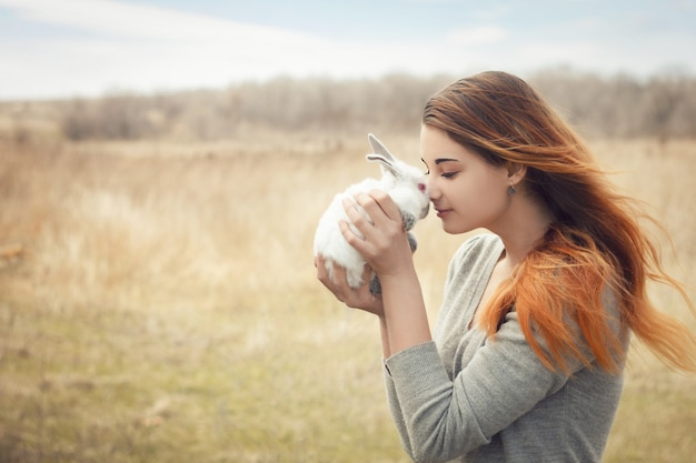 La fille avec le lapin. heureuse petite fille tenant un joli lapin moelleux