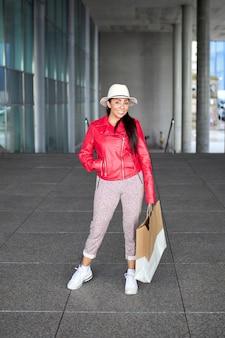 Fille latina en veste rouge souriant avec sac à provisions à l'extérieur.