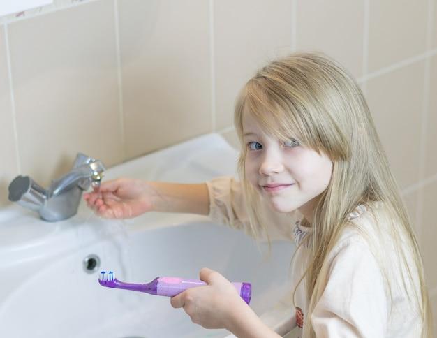 Une fille lave une brosse à dents électrique dans la salle de bain.
