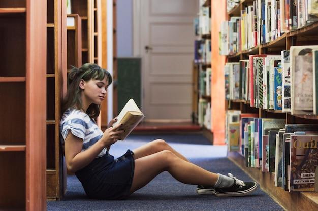 Fille de lecture assise sur le sol de la bibliothèque