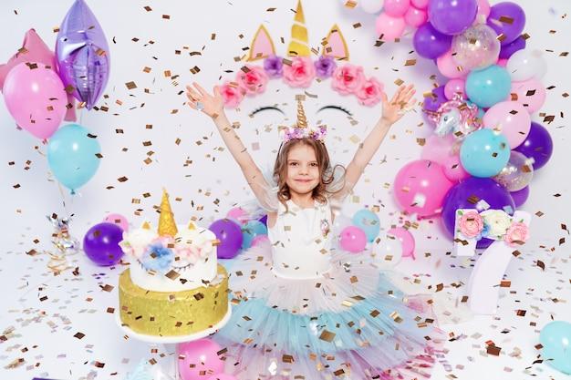 Fille licorne jette des confettis à la fête d'anniversaire