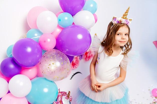 Fille de licorne posant près de l'idée de ballons d'air pour décorer unicor