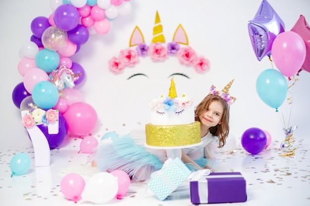 Fille de licorne posant près de l'idée de gâteau joyeux anniversaire pour la décoration