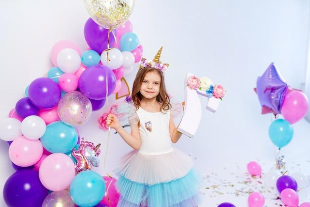 Fille de licorne tenant une idée de ballon et lettre air confetti or
