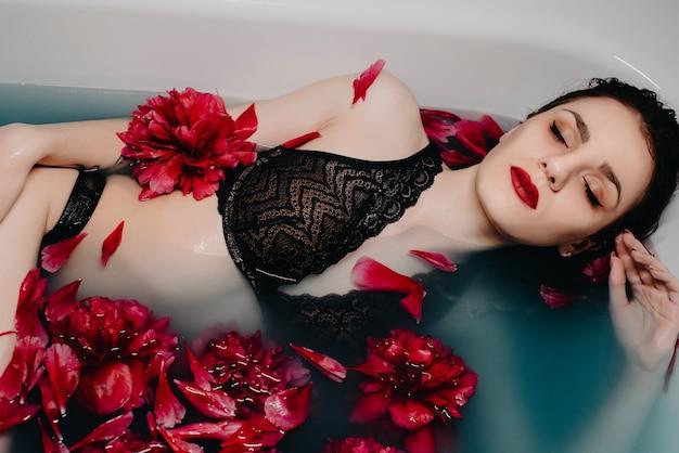 Fille en lingerie aime dans le bain avec des pétales de fleurs