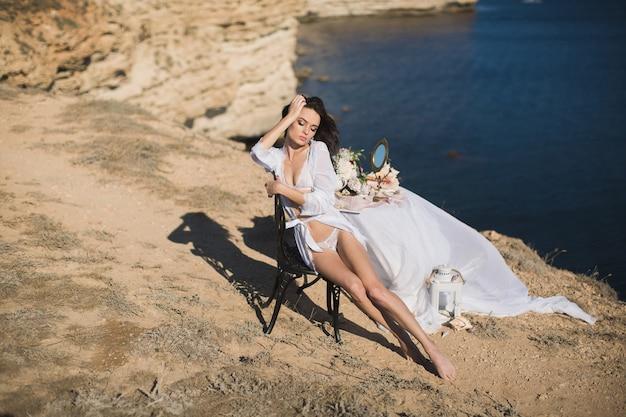 Fille en lingerie au sommet d'une montagne surplombant l'océan. charges de la mariée, le matin de la mariée.