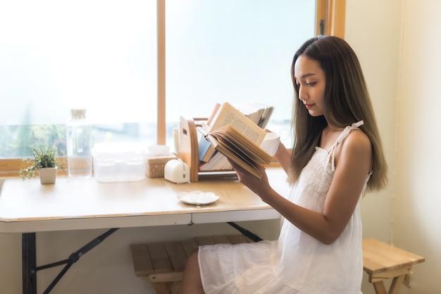 Fille lire livre et boire du café près de la fenêtre