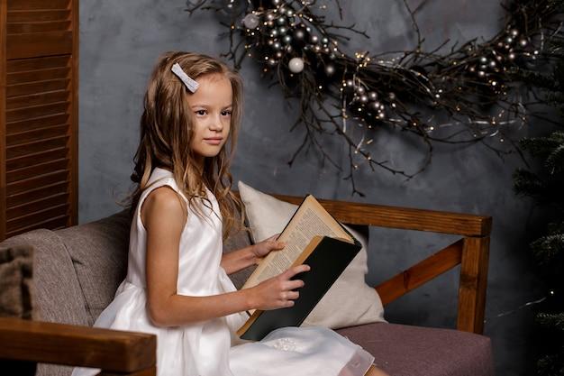 Fille lire un livre dans un salon décoré avec arbre de noël