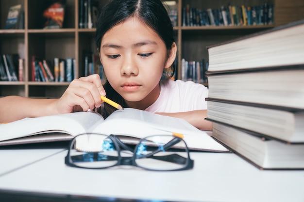 Fille lisant et écrivant et fait ses devoirs dans la bibliothèque