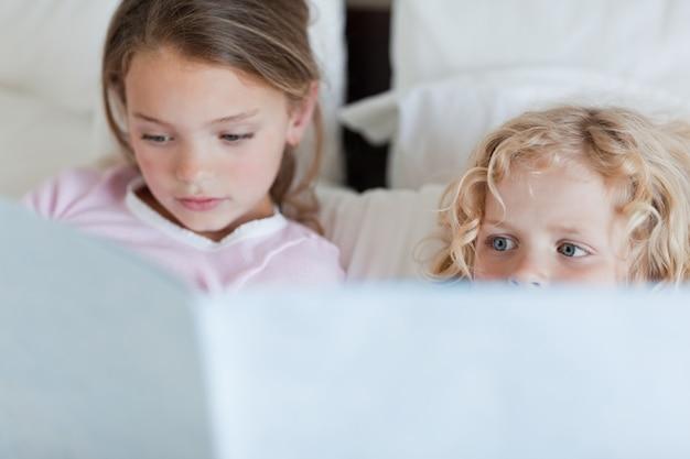 Fille lisant une histoire de temps de lit pour son frère