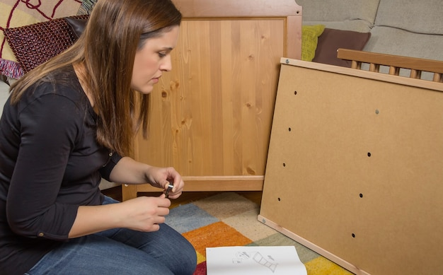 Fille lisant des instructions pour assembler des meubles