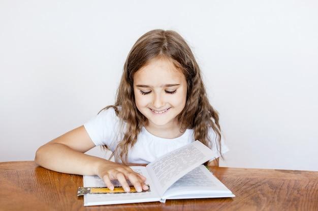 Fille lisant un livre assis à la table, classes, tâches, école, apprentissage à la maison, connaissances