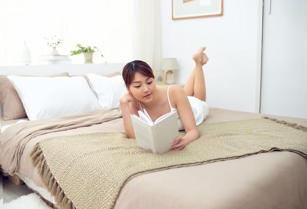 Fille lisant un livre au lit, allongé sur le lit souriant heureux et détendu.