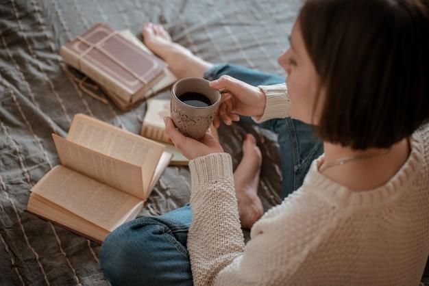 Fille lisant un livre et buvant du café au lit les pieds sur le mur.