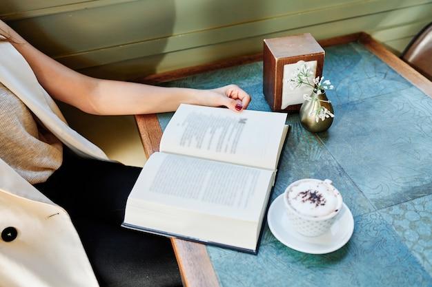 Fille lisant un livre dans un café