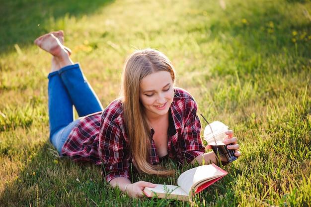 Fille lisant un livre dans un parc d'été
