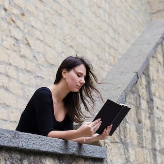 Fille lisant un livre dans la rue