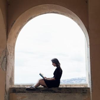 Fille lisant un livre sur une fenêtre