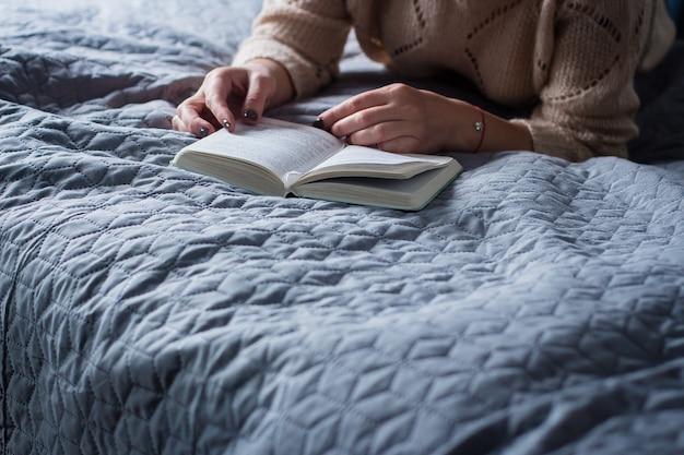 Fille lisant un livre sur un lit confortable gris. concepts de maison.