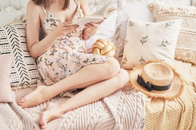 Fille lisant un livre à la maison sur un lit clair