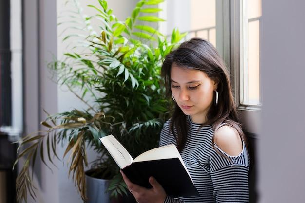 Fille lisant un livre à la maison