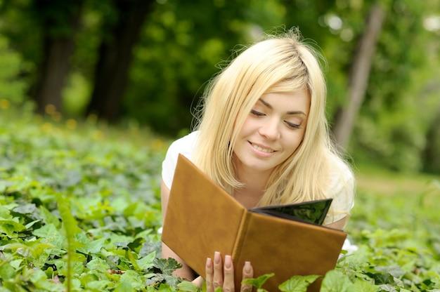 Fille lisant un livre en plein air.