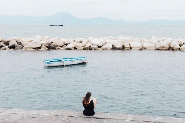 Fille lisant un livre sur le quai