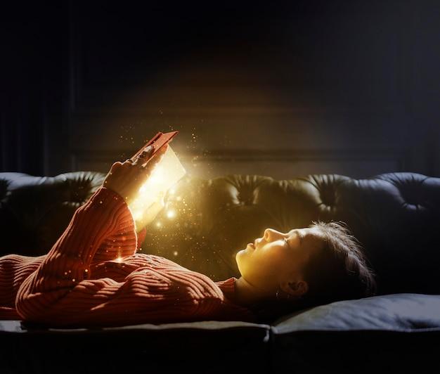 Fille lisant d'un livre rougeoyant magique
