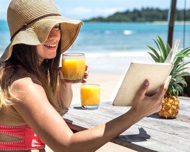 Une fille lit un livre au bord de la mer