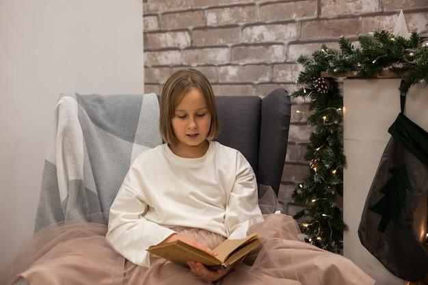 Une fille lit un livre sur une chaise à côté de la cheminée, flou artistique