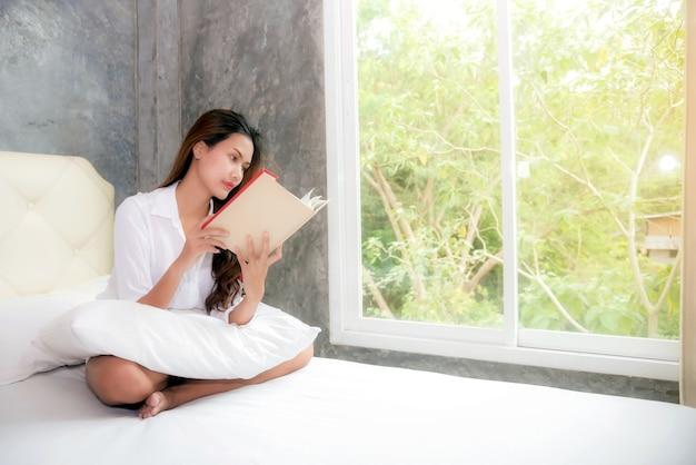 La fille lit le livre dans son lit après le réveil
