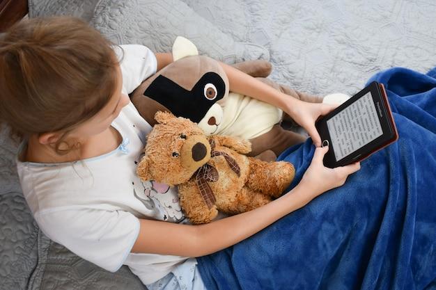 Fille lit un livre électronique
