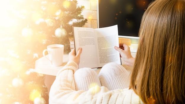 Fille lit un livre en hiver et s'assoit près de l'arbre de noël.