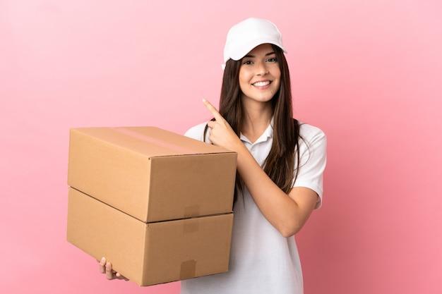 Fille de livraison mur rose isolé pointant sur le côté pour présenter un produit