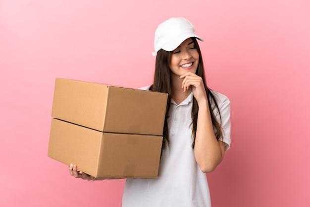 Fille de livraison mur rose isolé regardant sur le côté et souriant