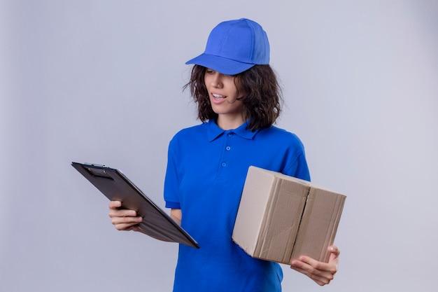 Fille de livraison en uniforme bleu et cap tenant le paquet de boîte et regardant le presse-papiers avec le sourire sur le visage debout sur blanc