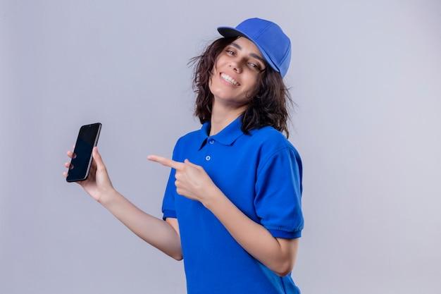 Fille de livraison en uniforme bleu et cap tenant le téléphone mobile et pointant avec l'index vers lui souriant joyeusement debout sur blanc